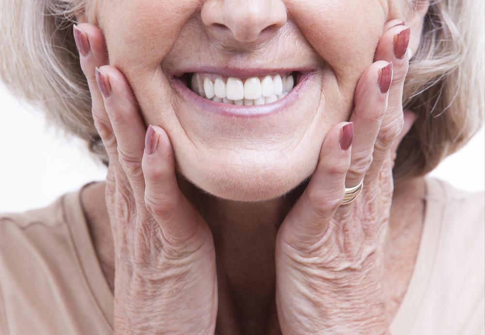 femme heureuse avec la copie de son dentier